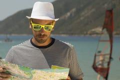 Hombre joven que mira el mapa en la playa Foto de archivo libre de regalías