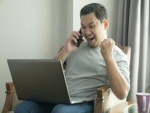 Hombre joven que mira el ordenador port?til, gesto que gana fotos de archivo