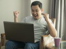 Hombre joven que mira el ordenador port?til, gesto que gana imagen de archivo libre de regalías