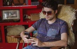 Hombre joven que mira el smartphone que se sienta en silla Fotografía de archivo