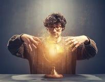 Hombre joven que mira en la bola de cristal que brilla intensamente imagenes de archivo