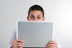 Hombre joven que mira a escondidas sobre el ordenador portátil Imagen de archivo libre de regalías
