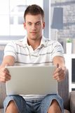 Hombre joven que mira fijamente la pantalla de la computadora portátil horrorizada Fotografía de archivo