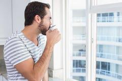 Hombre joven que mira hacia fuera su ventana Foto de archivo libre de regalías