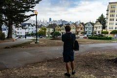Hombre joven que mira hacia señoras pintadas con la luz de calle en el Sa Fotos de archivo libres de regalías