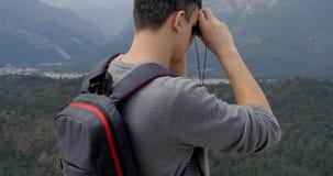 Hombre joven que mira la ciudad abajo almacen de video