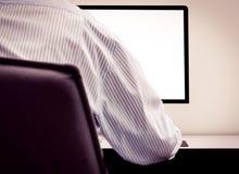 Hombre joven que mira la pantalla de ordenador vacía Imagenes de archivo