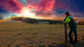 Hombre joven que mira a la puesta del sol de la nebulosa, manipulación de la foto fotografía de archivo libre de regalías
