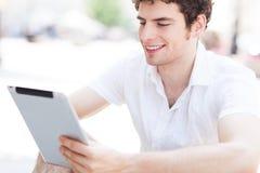 Hombre joven que mira la tableta digital Imagenes de archivo