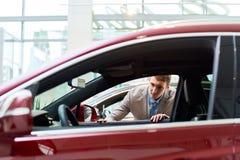 Hombre joven que mira los coches en la sala de exposición Fotografía de archivo libre de regalías