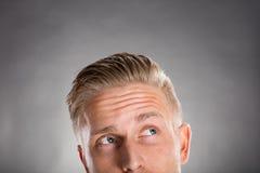 Hombre joven que mira para arriba contra Gray Background Fotografía de archivo