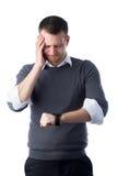 Hombre joven que mira preocupado el reloj Imagen de archivo libre de regalías