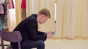 Hombre joven que mira smartphone mientras que su muchacha cambia la ropa en sitio apropiado almacen de metraje de vídeo