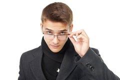 Hombre joven que mira sobre los vidrios Fotos de archivo libres de regalías