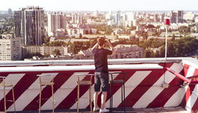 Hombre joven que mira a través de los prismáticos en el tejado de un edificio Imágenes de archivo libres de regalías