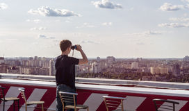 Hombre joven que mira a través de los prismáticos en el tejado de un edificio Fotografía de archivo libre de regalías