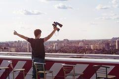 Hombre joven que mira a través de los prismáticos en el tejado de un edificio Imagen de archivo