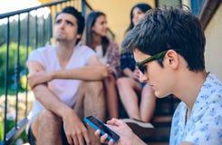 Hombre joven que mira un smartphone al aire libre con el suyo Fotos de archivo libres de regalías