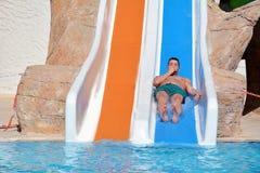 Hombre joven que monta abajo de un diapositiva-hombre del agua que disfruta de un paseo del tubo del agua Imágenes de archivo libres de regalías