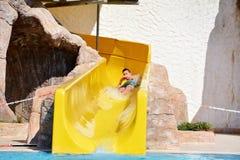 Hombre joven que monta abajo de un diapositiva-hombre del agua que disfruta de un paseo del tubo del agua Imagenes de archivo