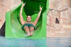 Hombre joven que monta abajo de un diapositiva-hombre del agua que disfruta de un paseo del tubo del agua Fotos de archivo
