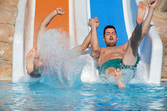 Hombre joven que monta abajo de un diapositiva-hombre del agua que disfruta de un paseo del tubo del agua Foto de archivo