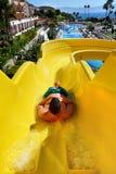 Hombre joven que monta abajo de un tobogán acuático Imagen de archivo