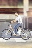 Hombre joven que monta la bicicleta eléctrica Imagen de archivo libre de regalías