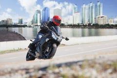 Hombre joven que monta la motocicleta grande de la bici en el camino de ciudad contra urbano Foto de archivo