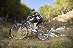 Hombre joven que monta una bici de montaña Imagen de archivo libre de regalías
