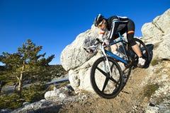 Hombre joven que monta una bici de montaña Fotografía de archivo libre de regalías