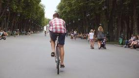 Hombre joven que monta una bicicleta del vintage en el callejón del parque Ciclo deportivo del individuo al aire libre Forma de v almacen de video