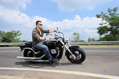 Hombre joven que monta una motocicleta en un camino abierto Fotos de archivo