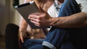 Hombre joven que muestra algo a su novia en la tableta en la Navidad almacen de video