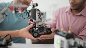 Hombre joven que muestra el nuevo dispositivo robótico al colega