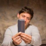 Hombre joven que muestra el teléfono Imagen de archivo libre de regalías