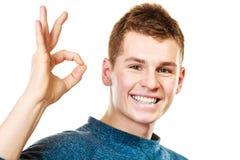 Hombre joven que muestra gesto aceptable de la muestra de la mano Imagen de archivo libre de regalías
