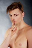 Hombre joven que muestra gesto silencioso Imagen de archivo