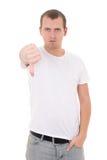 Hombre joven que muestra los pulgares abajo aislados en blanco Foto de archivo libre de regalías
