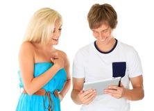 Hombre joven que muestra a muchacha su ordenador de la tablilla Imagenes de archivo