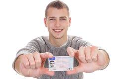 Hombre joven que muestra su carné de conducir Imagen de archivo libre de regalías