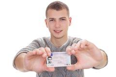 Hombre joven que muestra su carné de conducir Foto de archivo libre de regalías