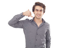 Hombre joven que muestra un gesto de la llamada de teléfono Fotografía de archivo