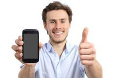 Hombre joven que muestra una pantalla elegante en blanco del teléfono con los pulgares para arriba Fotos de archivo