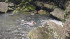 Hombre joven que nada en el río pedregoso en el hombre turístico del bosque tropical que goza del agua dulce que fluye en selva t almacen de metraje de vídeo