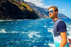 Hombre joven que navega abajo de los acantilados del Na Pali Foto de archivo