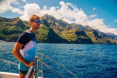 Hombre joven que navega abajo de los acantilados del Na Pali Fotografía de archivo libre de regalías