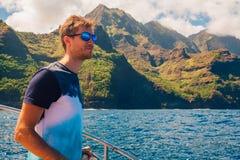 Hombre joven que navega abajo de los acantilados del Na Pali Fotos de archivo libres de regalías