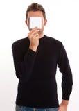 Hombre joven que oculta detrás de una nota Imágenes de archivo libres de regalías