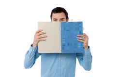 Hombre joven que oculta su cara con el cuaderno imagen de archivo libre de regalías
